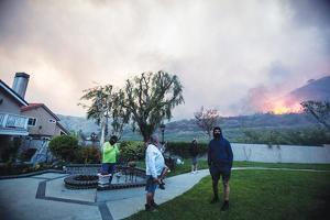 지난해 오렌지카운티 요바린다 시에서 발생한'블루릿지' 산불을 주민들이 뒷마당에서 걱정스럽게 바라보고 있다. <로이터>
