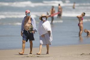 델타 변이의 확산으로 백신 접종자들도 여전히 주의를 해야 한다. 델마 해변을 찾은 주민들이 마스크를 쓰고 백사장을 거닐고 있다.   <로이터>